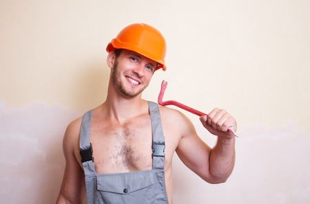 dismantling: A man in overalls and helmet with a tool for dismantling