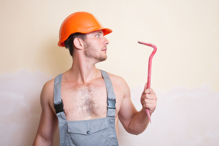 A man in overalls and helmet with a tool for dismantling