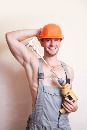 only man: A man in overalls and helmet with a mixer for plastering