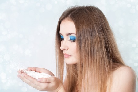 frozen winter: Girl with bright blue make-up blowing on snow in hands