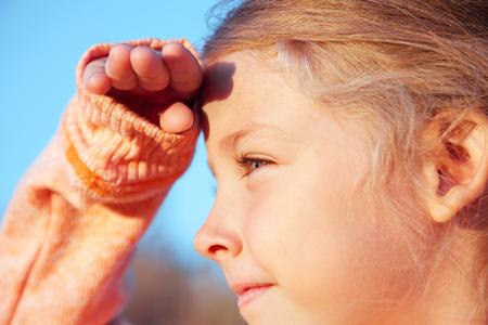 far away look: The little girl looks away, portrait on nature