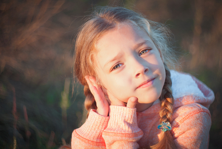 sad cute baby: The girl with blue eyes looking up thoughtfully Stock Photo