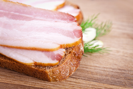 raw bacon: Sandwich with raw bacon on a wooden chopping board Stock Photo