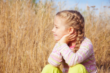 far away look: Portrait of a girl with pigtails on a sunny day outdoors Stock Photo