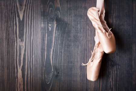 ballet dance: Pink ballet shoes on a wooden background Stock Photo