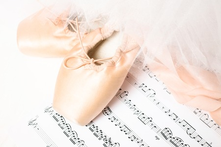 Ballet shoes, skirt and music sheet on a white background
