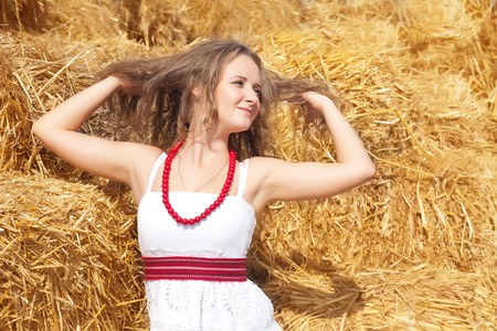 hayloft: Portrait of a beautiful young woman dressed in country style on a background of hay