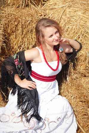 sundress: Beautiful young woman in a scarf and a white sundress near haystack in summer sunny day