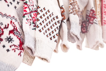 Several pairs of knitted woolen socks on a white background