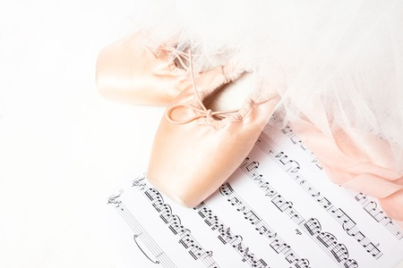 sheet music: Ballet shoes, skirt and music sheet on a white background