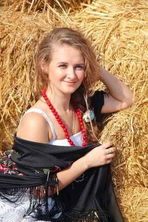 hayloft: Young smiling beautiful young woman in a white sundress on a haystack in the summer on a bright sunny day