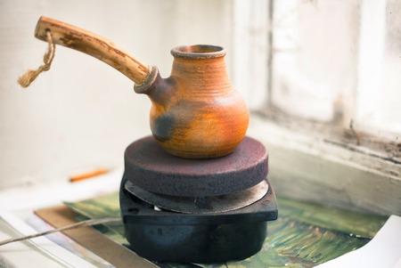 cezve: Cezve of coffee on a small stove on a windowsill near the old window