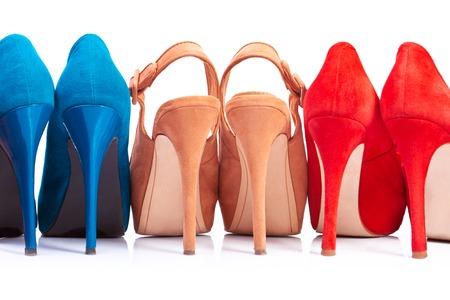 Tre paia di scarpe da donna con tacchi su un fondo bianco