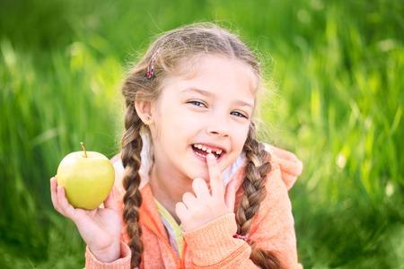 fille douce avec un toth tombé tenant une pomme dans sa main sur la nature