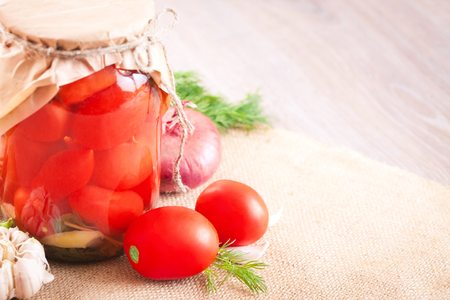 Canned tomatoes with garlic and herbs in a glass jar on the wooden table Stock Photo