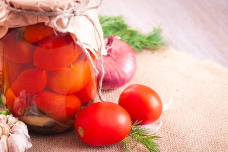 sterilized: Canned tomatoes with garlic and herbs in a glass jar on the wooden table Stock Photo