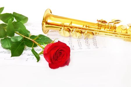 soprano saxophone: Rosa roja, saxofón y notas sobre un fondo blanco