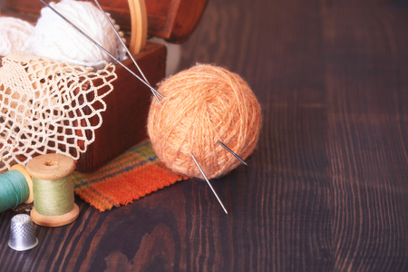needle lace: Casket with needlework and beige skein of thread with spokes for knitting on a wooden table