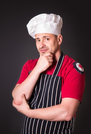 profess: Portrait of a chef with a sad expression on his face in the studio on a black background Stock Photo