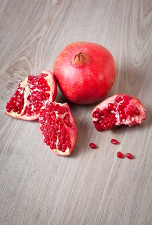Close up sliced and whole pomegranate on a table Stock Photo