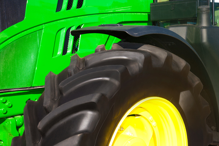 Tire on green tractor close up in the foreground