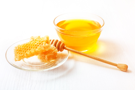 Honey with a wooden spoon on a white table