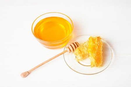 drizzler: Honey with a wooden spoon on a white table
