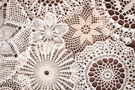Beautiful delicate vintage lace background of crochet napkins on the table close up