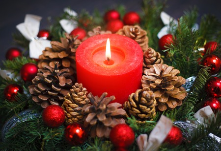 Decorated Christmas wreath with a candle close-up on a table