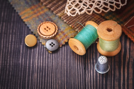 Thimble, buttons, spools of thread and fabric swatches on a wooden background close up
