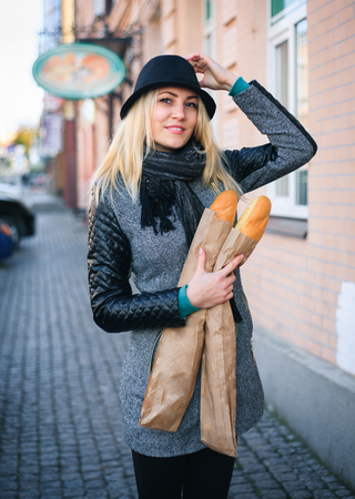 Young beautiful woman with a loaf of bread in her hands in autumn. Outdoors portrait. Stock Photo