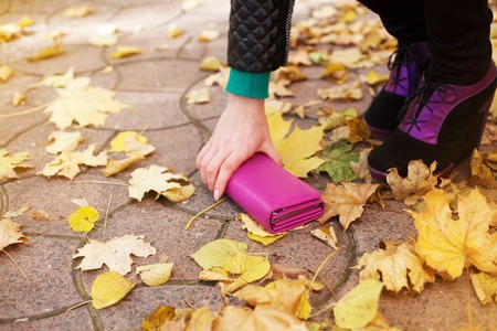 possession: Woman raises a lost wallet on the street in autumn day