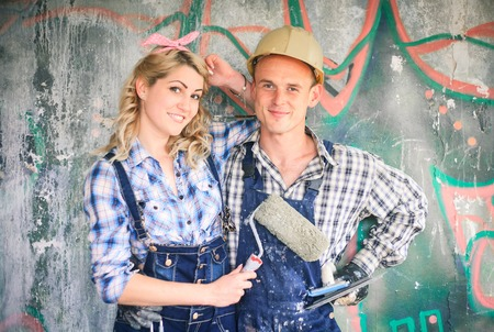 housepainter: Portrait of a young man and woman in overalls with tools for the repair of the interior in hands. Concept of construction and home repair. Stock Photo