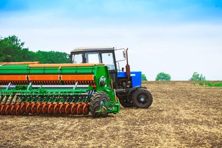 harrow: Tractor with a harrow to work the land field Stock Photo