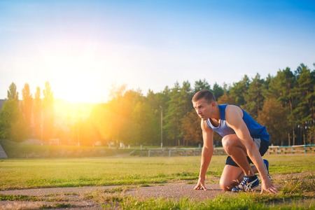 Man in low start position on old stadium. Athlete in starting position. Running, jogging, cardio, sport, active lifestyle concept.