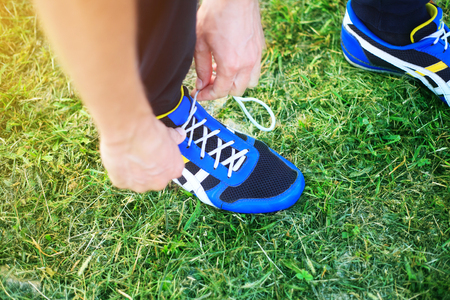 sport shoe: Man laces shoelaces in running shoes closeup