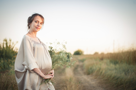 lovely pregnant woman: Portrait of a pregnant woman in the sunset light on the nature of the field