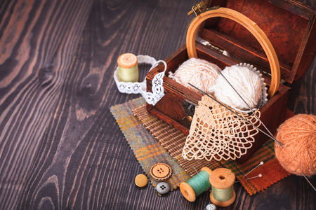needle laces: Spool of thread, a thimble and a box with needlework on a wooden table close-up