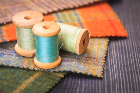 Spools of thread and fabric swatches on the table close up