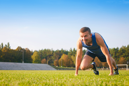 starting position: Man in low start position on old stadium. Athlete in starting position. Running, jogging, cardio, sport, active lifestyle concept.