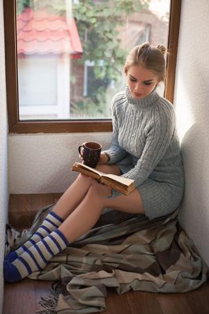 Young beautiful woman in a sweater reading a book near the window. Фото со стока