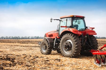 siembra: Red tractor trabajando en un campo en un día soleado.