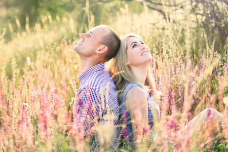 A handsome man and an attractive woman sitting on nature in flowers.
