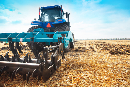 Modern tractor in a field on a sunny day.. The concept of work in a fields and agriculture industry. Stock Photo