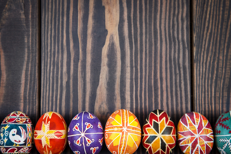 christian festival: Easter eggs in a row on a dark wooden background.