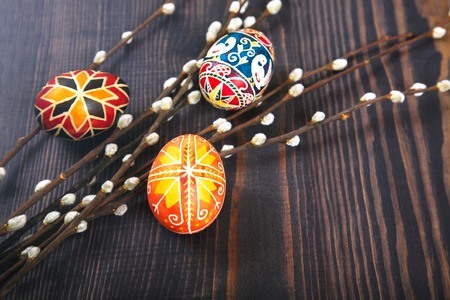 Easter eggs with willow twigs on a wooden plank table. The concept of the Easter holidays, and folk art.