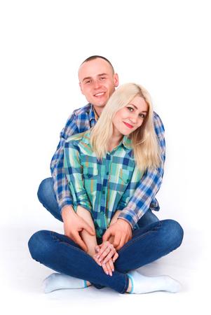 Romantic young couple sitting on floor cuddling, in studio.