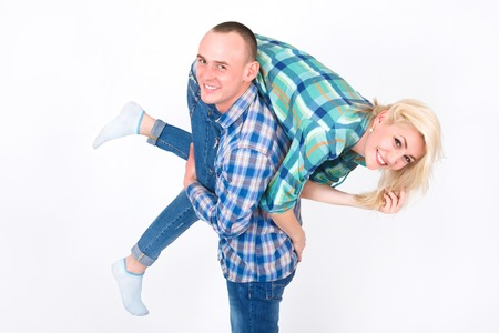 A young man carries a woman on his shoulder, in a studio on a white background.