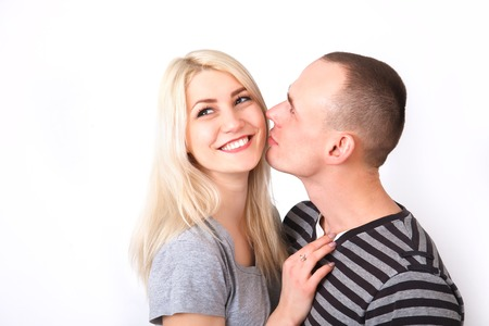 Careful man kissing his smiling girlfriend in a studio against a white background.