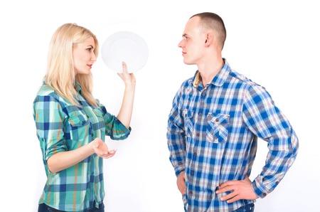 A man and a young woman with a plate in her hand quarrel in a studio on a white background.